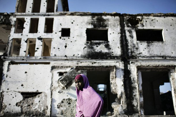 A Girl In Front Of A Bombed-Out Building