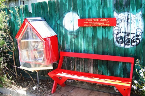 red plastic covered little free library and bench